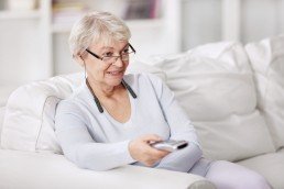 Greyhaired woman watches TV using WEar & Hear hearing aid