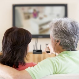 Man and Woman watch TV using HearLink PLUS
